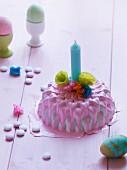Mini-Kuchen dekoriert mit rosa Zuckerglasur, Kerze & Papierblüten