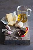 Stillleben mit Anchovis, Knoblauch, Butter und Öl
