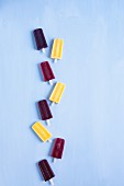 Blueberry, Rasberry and Mango Popsicles in a row