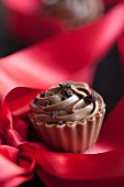 A chocolate praline on a red silk ribbon