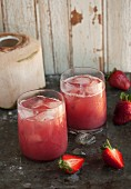 Strawberry and coconut water drinks with ice cubes