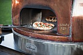 A margherita pizza being taken out of the wood-fired oven