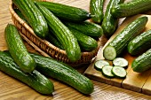 Fresh cucumbers in a basket and on a chopping board