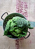A savoy cabbage in a vintage colander on a printed hessian coffee sack