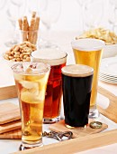 Assorted glasses of beer, cider and party snacks