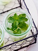 A glass of lemonade with fresh mint in a wire basket