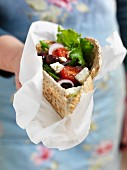 A woman holding a pita bread filled with Greek salad