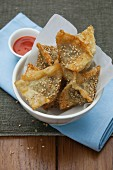 Deep-fried pastry parcels with sesame seeds and chilli sauce (Asia)
