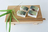 Oshi sushi with mackerel on a wooden slab