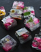 Several ice cubes containing edible flowers