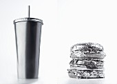 A cardboard drinks container and a hamburger (silver-coloured)