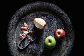 Three apples with a peeler on a stone plate
