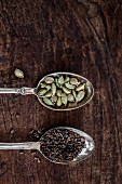 Cardamom on silver spoons on a wooden surface