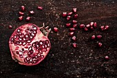 Half a pomegranate and pomegranate seeds on a wooden surface