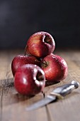 Red apples with droplets of water and a knife, on a wooden surface