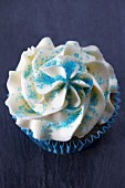 A cupcake with buttercream icing and blue sugar