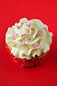 A cupcake with buttercream icing and sugar hearts for Valentine's Day