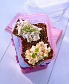 Smoked trout cream and an apple and leek spread on wholemeal bread in a Tupperware container