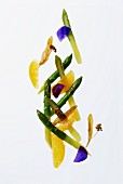 Green asparagus with orange segments and lime flowers