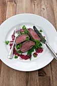Sliced saddle of venison on green bean salad with beetroot vinaigrette