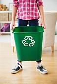 Junge trägt Abfallbehälter mit Recylingsymbol