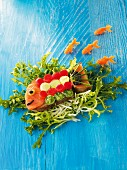 A fish made from bread, salmon and vegetables