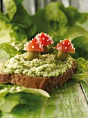 A slice of bread topped with spinach pâté and toadstools made from tomatoes and olives