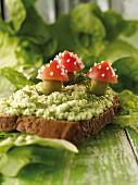 Belegtes Brot mit Spinatcreme und Fliegenpilzen aus Tomaten und Oliven