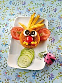 Breaded escalope of meat for a child, with a face made out of vegetables and chips