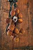 Lychees on a twig in front of a wooden wall