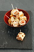 Rolled strips of pancake filled with smoked salmon, cheese and dill