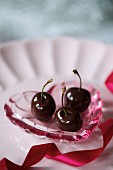 Chocolate-coated cherries on a heart-shaped dish for Valentine's Day