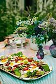 Sommersalat mit Tomaten und hartgekochten Eiern auf Gartentisch (Schweden)