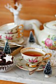 A cup of tea with a rose pattern and Christmas biscuits