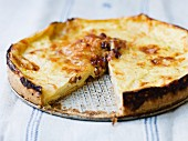 Cheese quiche, partly sliced