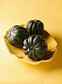 Three Whole Acorn Squash in a Shallow Yellow Bowl; Yellow Background