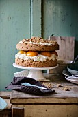 Peach layer cake with cream cheese filling and oat crumble topping