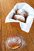 Doughnuts with icing sugar in and in front of a box