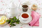 Peppermint tea, tea leaves, sugar and lemon slices