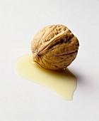 A walnut in a small pool of walnut oil