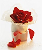 A still life featuring ramekins, a doily and a rose
