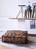 Bodenkissen mit Tierfellmuster auf Tierfellteppich und verschiedene Hocker auf rustikaler Ablage