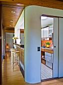 Kücheneinbau mit abgerundeter Ecke und offene Schiebetür mit Blick auf Küchenzeile, an der Seite Durchreiche und Thonet Barhocker