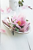 A place setting with a napkin, cutlery and a peony
