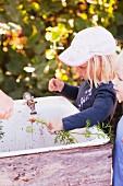 Kinder waschen Karotten in einem Spülbecken im Garten