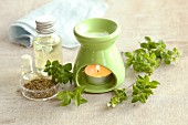 Marjoram oil and marjoram (fresh and dried) with a scented oil lamp