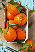 Several mandarins with leaves in a cardboard punnet on a chopping board
