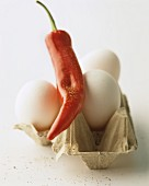 A still life featuring a chilli pepper and white hen's eggs in an eggbox