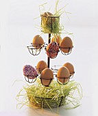 Brown hen's eggs and painted eggs with hay in an egg holder