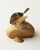 A partly sliced loaf of bread, and a scoop of cereal grains